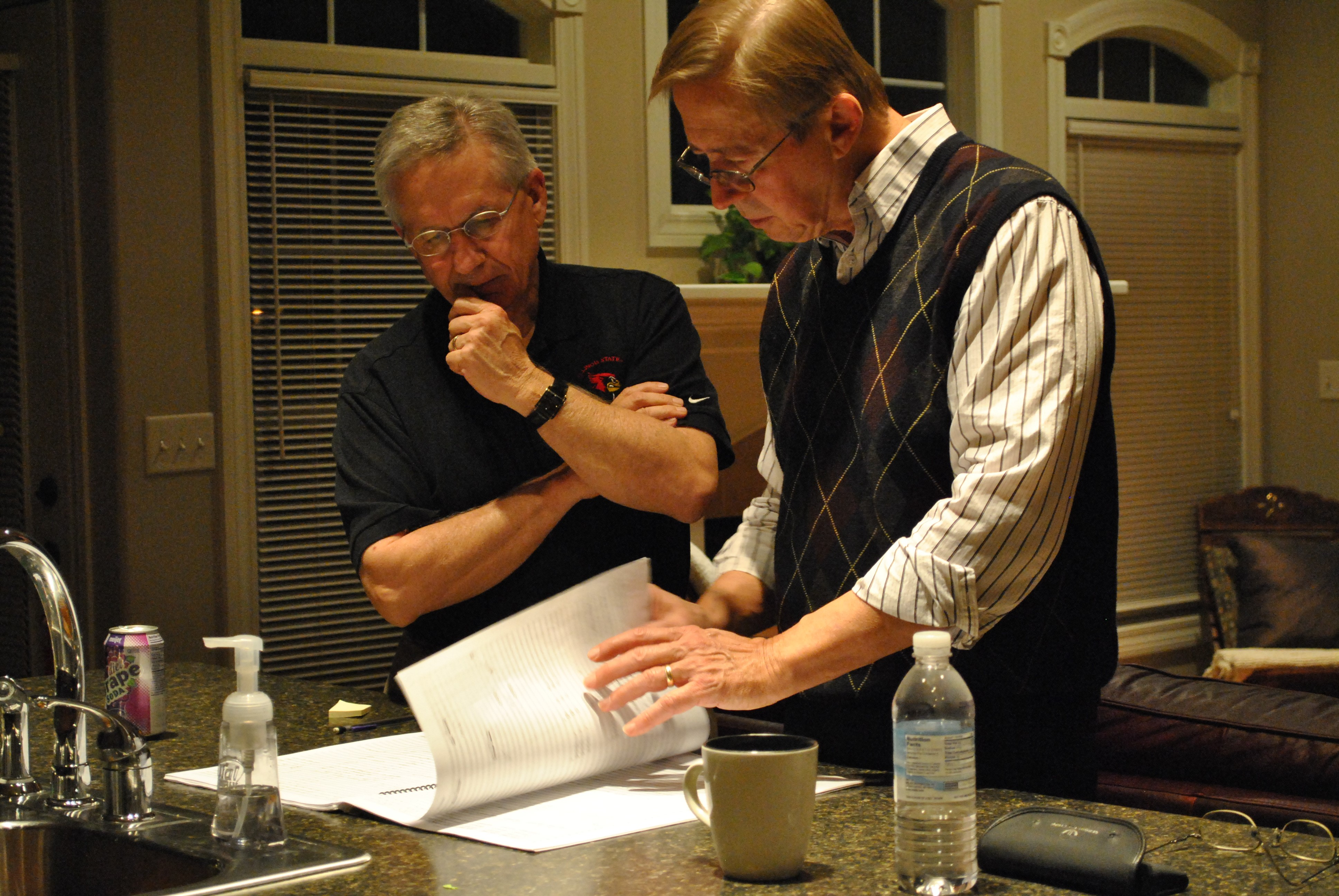 Stephen K. Steele and David Maslanka looking through one of his scores near a kitchen sink.
