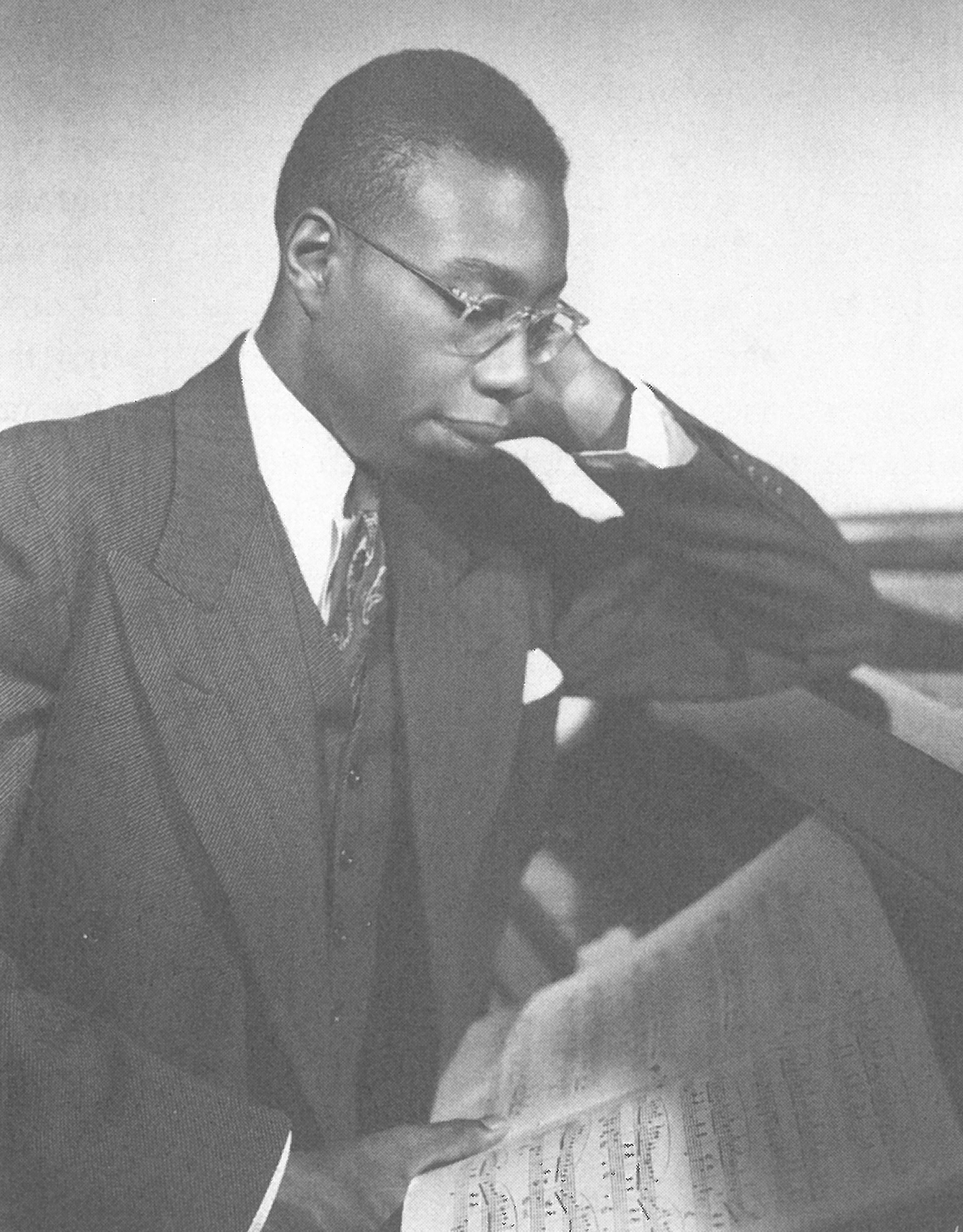 George Walker at a piano pensively studying a score in 1941.