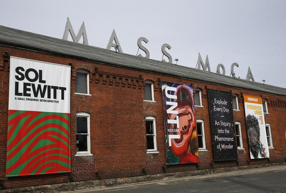 One of the outside walls of MASS MoCA which is partially covered with posters for exhibitions: Sol Lewitt, Federico Urbe, UNTL.